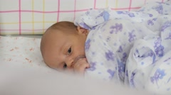 Blue-eyed baby in a crib covered with a sheet. Handheld shot Stock Footage