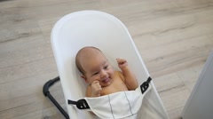 Healthy happy infant in a baby chair. Handheld shot Stock Footage