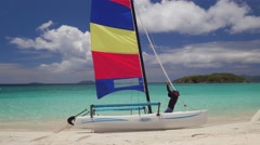 Man getting reading to sail a Catamaran at Cinnamon Bay, St John Stock Footage