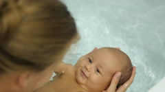 Young mother bathing with care little cute baby in a pure water. Handheld shot Stock Footage