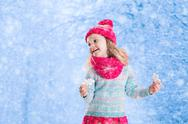 Little girl playing with toy snow flakes in winter park Stock Photos