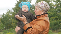 Early autumn. Baby dressed in a suit with a blue cap. Grandma in brown leather Stock Footage