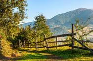 Fence on hillside meadow in mountain Stock Photos