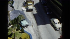 1962: large buildings on a hill with many vehicles parked in the surrounding Stock Footage