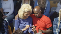4K Couple sitting in the crowd at sports event taking photos with smartphone Stock Footage
