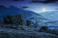 Fence on hillside meadow in mountain at night Stock Photos
