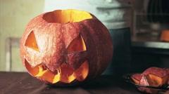 Freshly carved jack o lantern pumpkin on kitchen table Halloween theme close up Stock Footage
