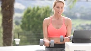 Fitness girl doing weight exercises in front of tablet Stock Footage