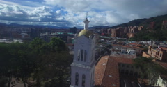 Spinning around the white clock tower of Usaquen's plaza church Stock Footage