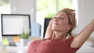 Portrait of beautiful middle-aged woman relaxing in office Stock Footage