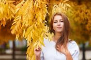 Beautiful young woman in autumn park with yellow leaves Stock Photos