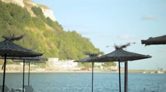 Parasols against the evening beach and mountain Stock Footage