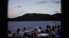 1962: passengers relax along a railing on ship moving near shoreline  Stock Footage