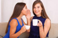 Happy friends talking, drinking coffee and tea Stock Photos