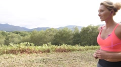 Beautiful athletic woman running in countryside Stock Footage