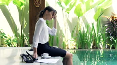 Sad, unhappy businesswoman reading documents by pool in outdoor villa Stock Footage