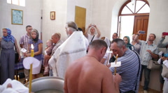 Baptism. People walk a circle around the baptismal font Stock Footage