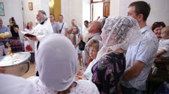 Baptism. The priest reads the prayer, there are people around Stock Footage