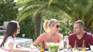 Friends having lunch outside on a sunny day Stock Footage