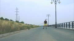 Young sporty man with inline skates ride and jump in summer waterfront Stock Footage