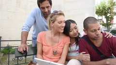 Friends on vacation looking at tourist information on tablet Stock Footage