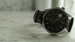 Black faced wrist watch set on a white marbled surface Stock Footage