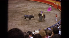 1962: a bull fighting a lancer on horseback during a bullfight at large audience Stock Footage