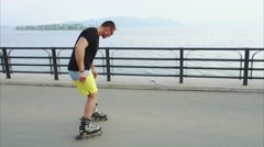 Young sporty man roller skating on summer seafront Stock Footage