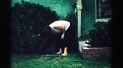 1957: a woman manipulating a faucet in a yard full of greenery in a house  Stock Footage