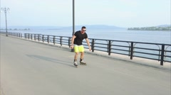Young sporty man learns to roller skate and jump on waterfront Stock Footage