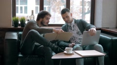Two entrepreneurs working and taking notes together in table of a little office Stock Footage