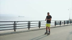 Young sporty man roller skating and drink water from the bottle on waterfront Stock Footage
