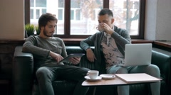 Two entrepreneurs working and taking notes together in table of little office Stock Footage