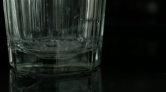 Pouring clear water into a clear glass against black background Stock Footage