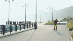 Young sporty man roller skating on summer waterfront Stock Footage