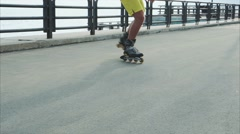 Mans legs roller skating inline close up on the waterfront Stock Footage