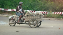 Vietnamese laborer transporting bags of cement on cargo tricycle in Nha Trang Stock Footage