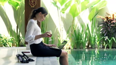 Young businesswoman working on laptop and drinking wine by pool in outdoor villa Stock Footage