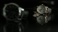 Two Wrist Watches set on a dark reflective surface with depth of field  Stock Footage