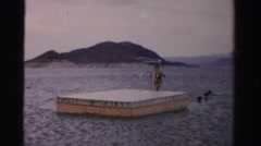 1957: a woman climbs the ladder at a floating dock with other swimmers nearby Stock Footage