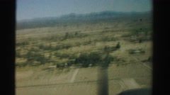 1957: view from airplane of dry desert farmland and trees with mountains  Stock Footage