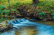 Autumn landscape with flowing river and leaves Stock Photos