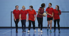 4K Female sports teacher coaching young female team on indoor soccer pitch Stock Footage