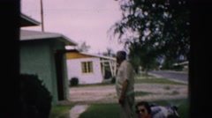 1957: an old man strolling behind two ladies sitting on the lawn LAS VEGAS Stock Footage