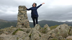 Woman climbs and reaches mountain summit Stock Footage