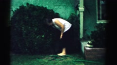 1957: an older woman is bending down and reaching for something under a bush  Stock Footage
