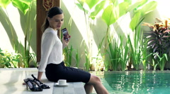 Happy businesswoman listening to music on cellphone by pool in outdoor villa Stock Footage