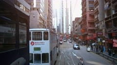 Electric cable cars and personal vehicles on typical urban street in Hong Kon Stock Footage