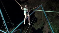 Girl playing bungee jumping trampoline outside at night Stock Footage