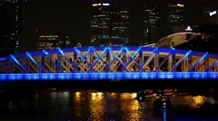 Beautiful, lighted bridge over the Singapore River at night Stock Footage